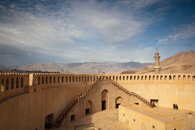 Bedöva sikten av det Nizwa fortet som omges av berg royaltyfri fotografi