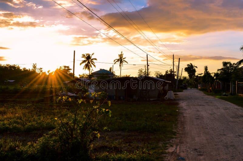 Bedöva sikten av solen som ställer in över lantligt liv på ön av Cebu, Filippinerna royaltyfri fotografi