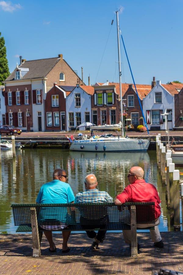 Bedöva sikter över den historiska holländska yachthamnen som hålls ögonen på av höga män som sitter på bänk arkivfoto