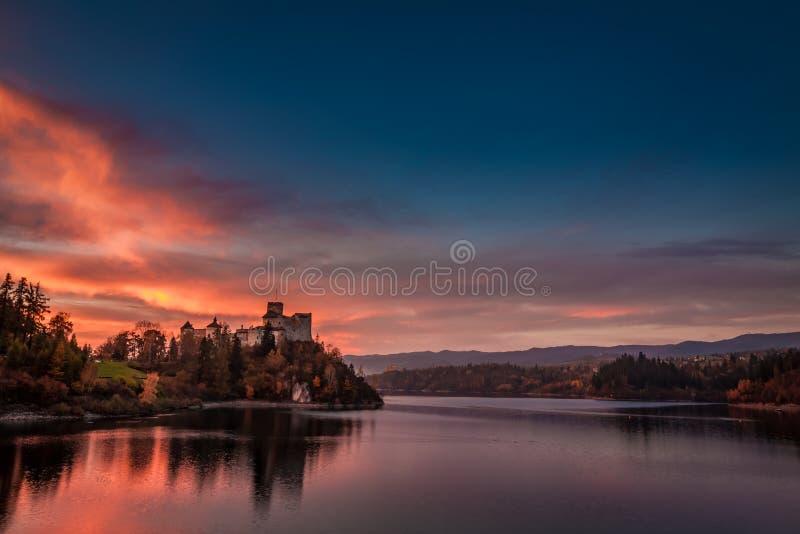 Bedöva skymning över slott vid sjön i Niedzica fotografering för bildbyråer