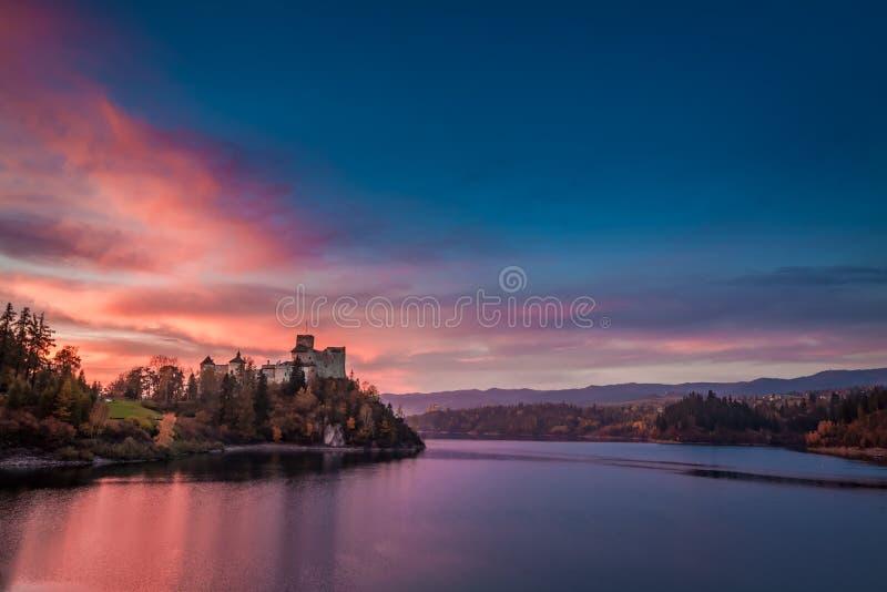 Bedöva skymning över slott vid sjön, Polen royaltyfri fotografi