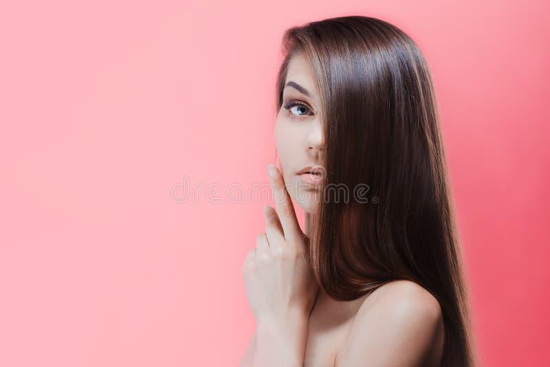Bedöva ung brunett med perfekt hår, på en rosa bakgrund Den unga asiatiska flickan som kammar hår med, fingrar isolerat på vitbak arkivbild