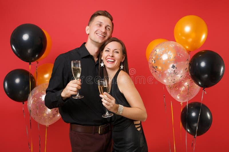 Bedöva unga par i svart kläder som firar födelsedagferiepartiet på ljusa röda bakgrundsluftballonger royaltyfria foton