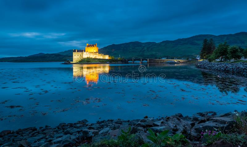 Bedöva upplysta Eilean Donan Castle på skymning i Skottland arkivfoton