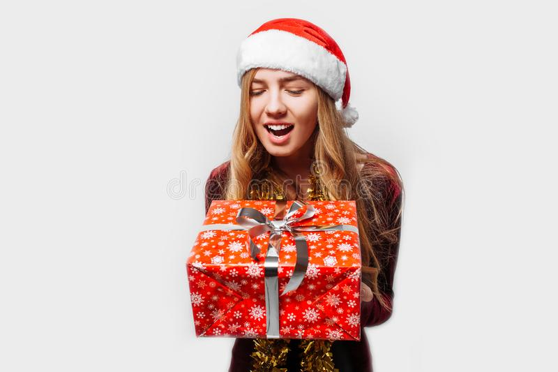 Bedövad flicka i en hatt av Santa Claus, i hennes händer - jul royaltyfria bilder