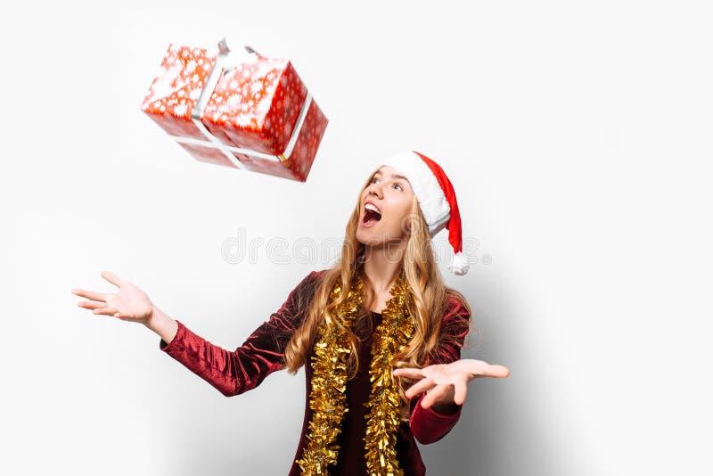 Bedövad flicka i en hatt av Santa Claus, i hennes händer - jul arkivfoto