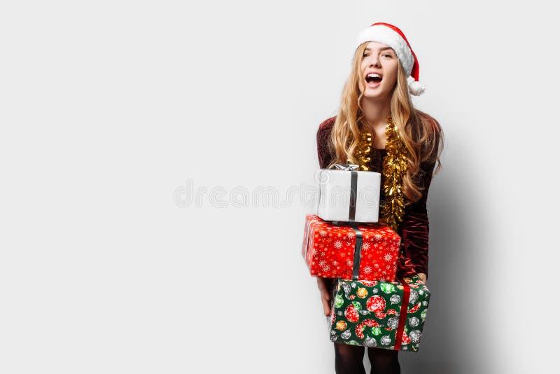 Bedövad flicka i en hatt av Santa Claus, i hennes händer mycket gåva arkivbilder