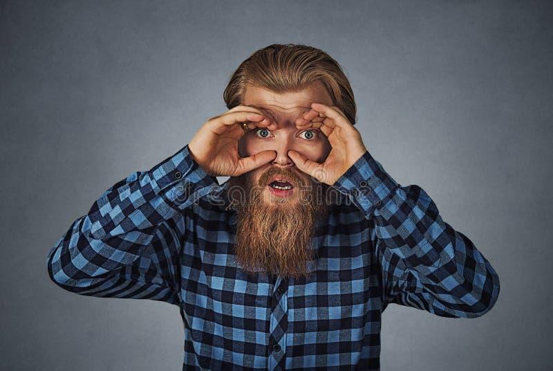 Bedövad nyfiken man som ser till och med fingrar som kikare royaltyfri foto