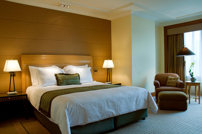 Bed and armchair in a 5 star suite bedroom stock image
