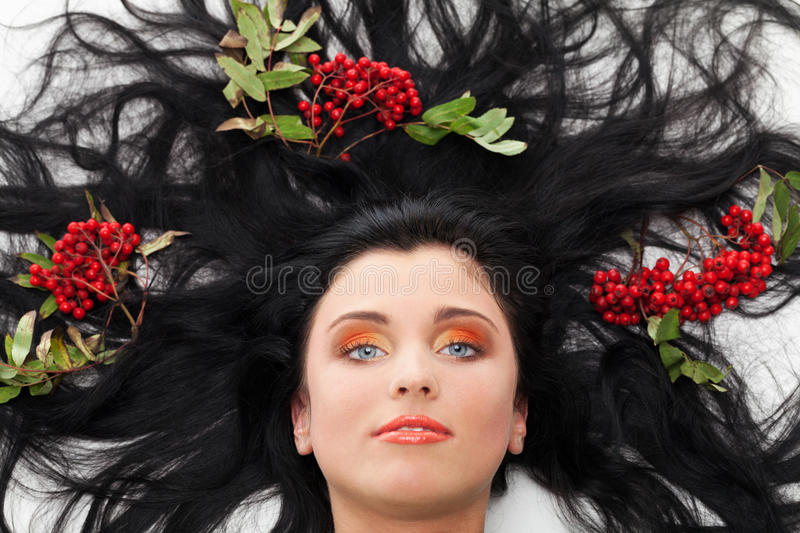 On a bed of ashberry. Girl lying on a bed with ashberry in hairs royalty free stock photography