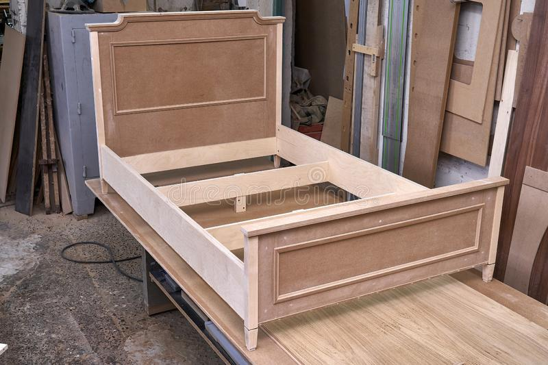 Bed building process. Wooden furniture manufacturing process. Furniture manufacture. Beautiful professionally made bed of plywood and MDF in process of stock photos