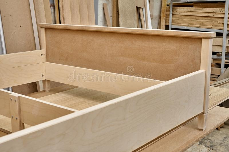 Bed building process. Wooden furniture manufacturing process. Furniture manufacture. Close-up. Beautiful professionally made bed of plywood and MDF in process of royalty free stock image
