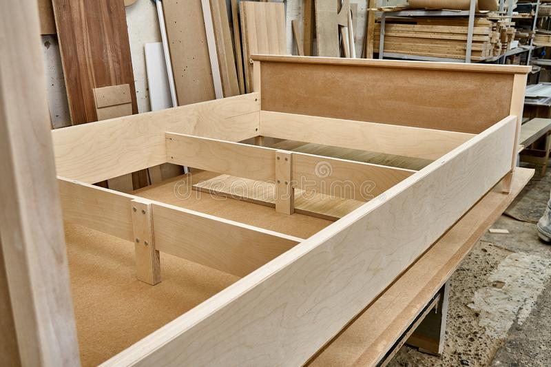 Bed building process. Wooden furniture manufacturing process. Furniture manufacture. Close-up. Beautiful professionally made bed of plywood and MDF in process of stock photography