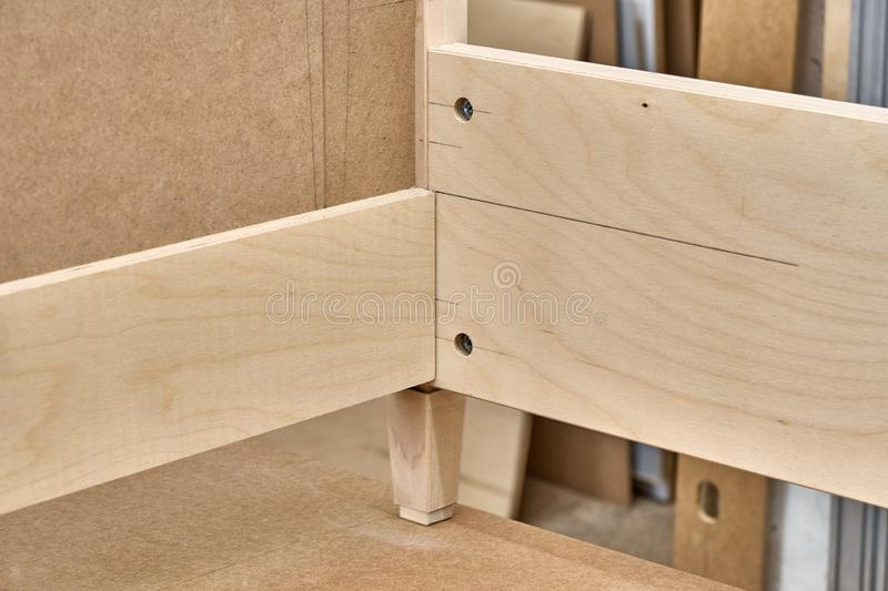 Bed building process. Wooden furniture manufacturing process. Furniture manufacture. Close-up. Beautiful professionally made bed of plywood and MDF in process of stock images