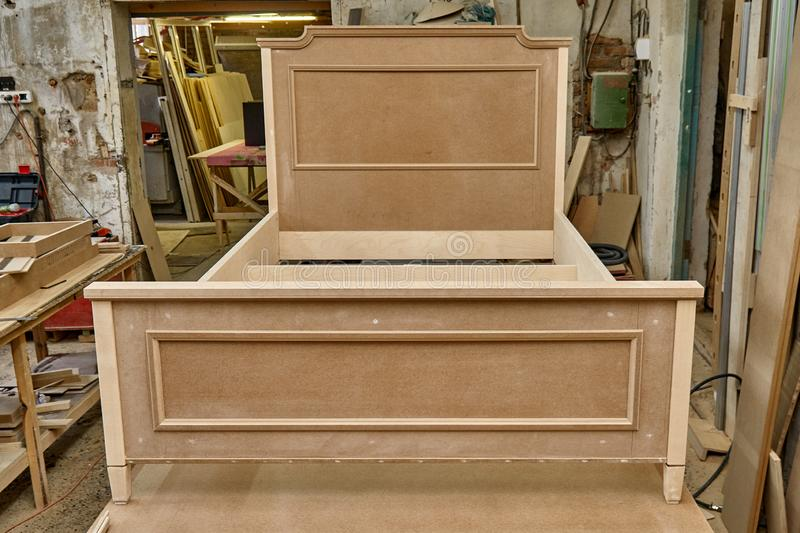 Bed building process. Wooden furniture manufacturing process. Furniture manufacture. Close-up. Beautiful professionally made bed of plywood and MDF in process of stock photo