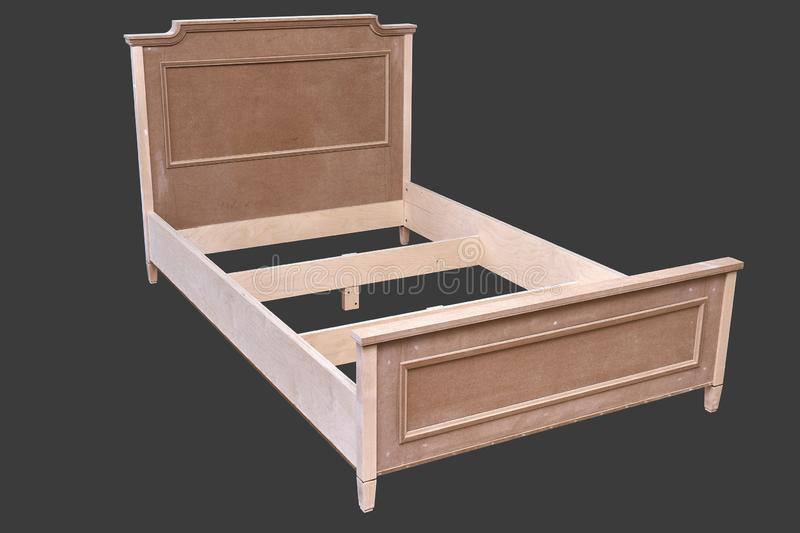 Bed building process. Wooden furniture manufacturing process. Furniture manufacture. Isolated on gray. Beautiful professionally made bed of plywood and MDF in stock photography