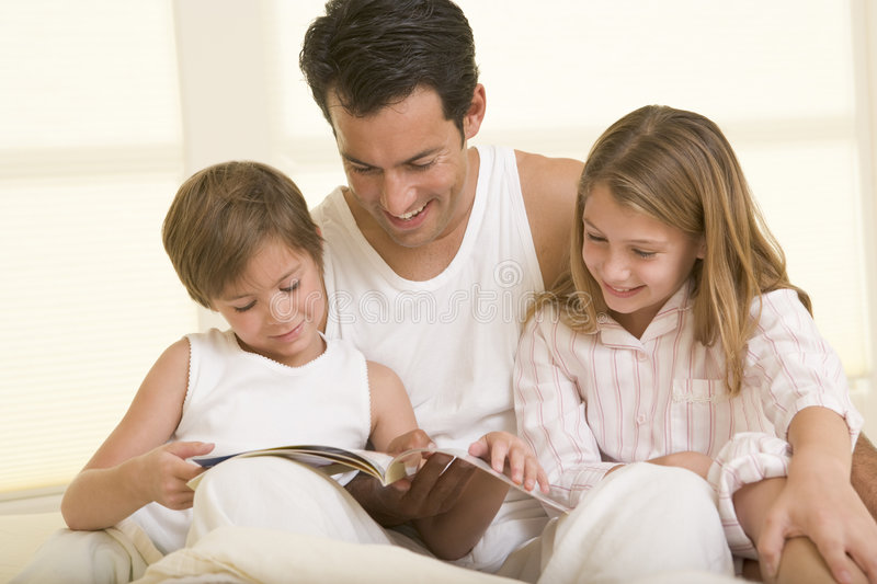 bed children man reading sitting two young