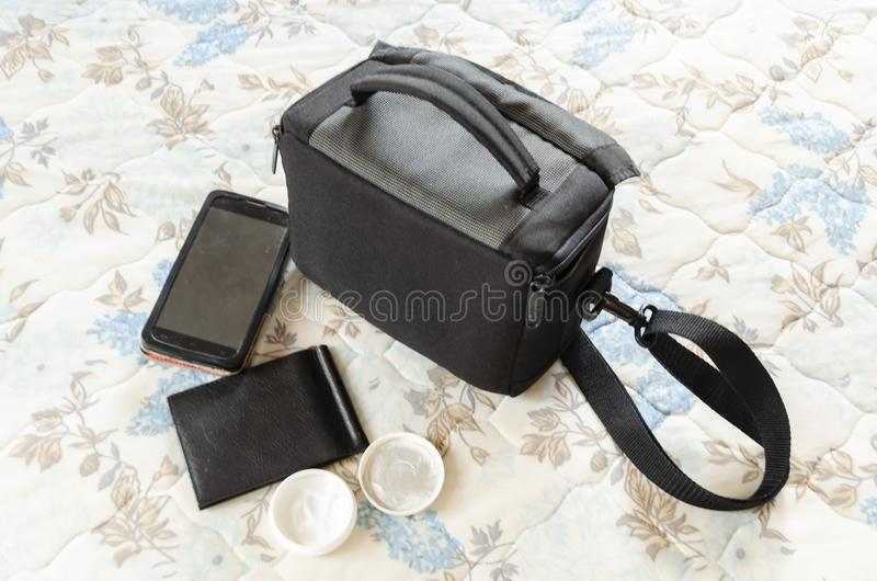 Camera Bag and Articles. On a bed covered with blue and white quilt spread is a black zipped camera bag with long strap, and short handle; a black mobile phone royalty free stock images