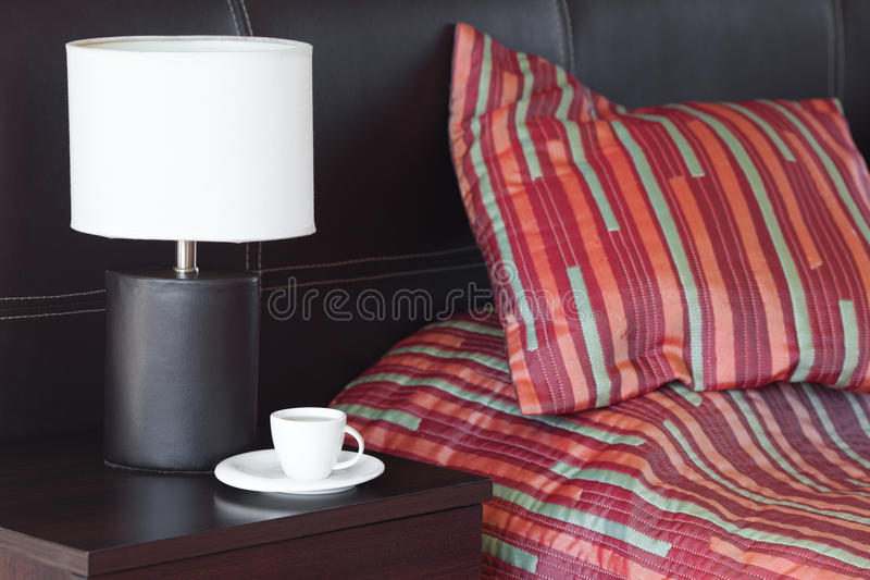 Bed , A Cup Of Tea On The Bedside Table And Lamp Royalty Free Stock Photos