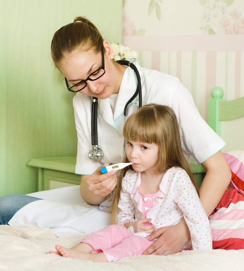 bed den små modern för flickan nära den sjuka sittande termometern royaltyfri fotografi
