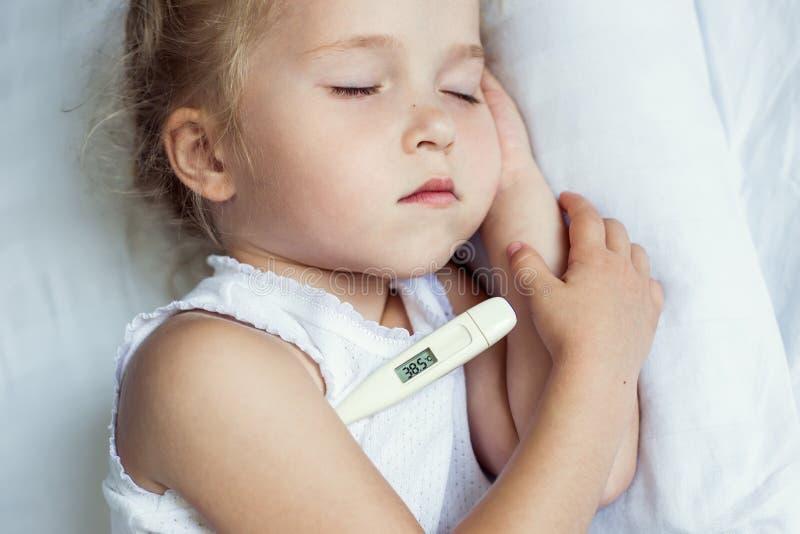 bed den små modern för flickan nära den sjuka sittande termometern arkivfoto