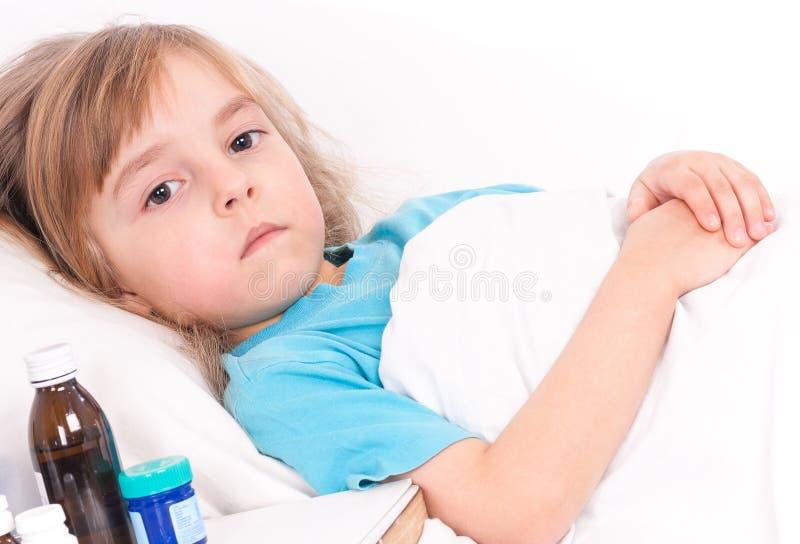 bed den små modern för flickan nära den sjuka sittande termometern royaltyfria foton
