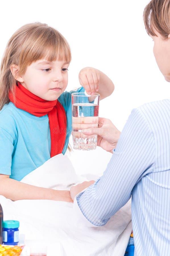 bed den små modern för flickan nära den sjuka sittande termometern arkivbilder
