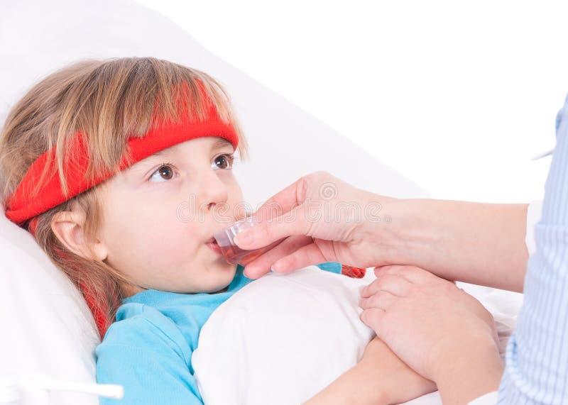 bed den små modern för flickan nära den sjuka sittande termometern arkivbild