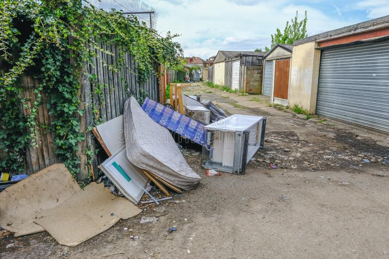 Bed, divan, fridge and freezer fly tipped in an alleyway. Large pile of rubbish, rotting after being fly tipped and left in an urban alleyway. Demonstrates anti royalty free stock images