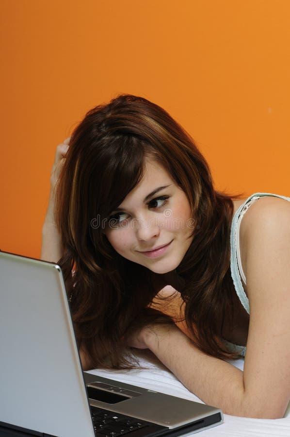 bed för flickabärbar dator för brunett gulligt använda arkivfoton