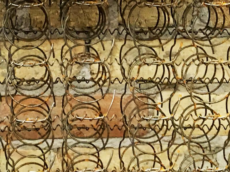 Bed Frame Springs Old. Old Coil Springs Bed Frame against a Brick Wall. Great Background antique stock photo