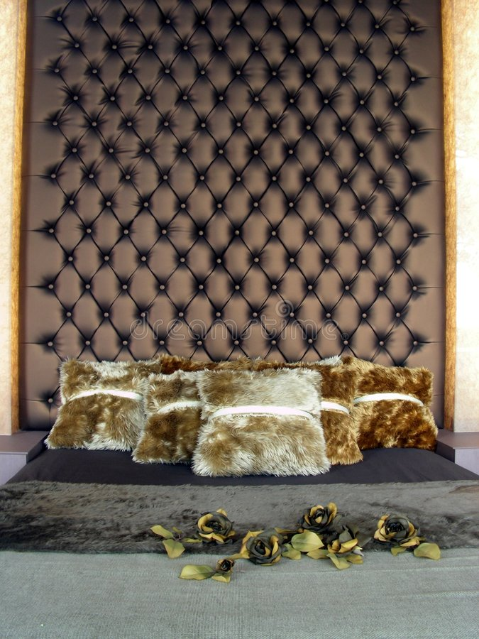 Bed with leather headboard. A very opulent bed with gold trim and silky soft square pillows. Pure resort living stock image