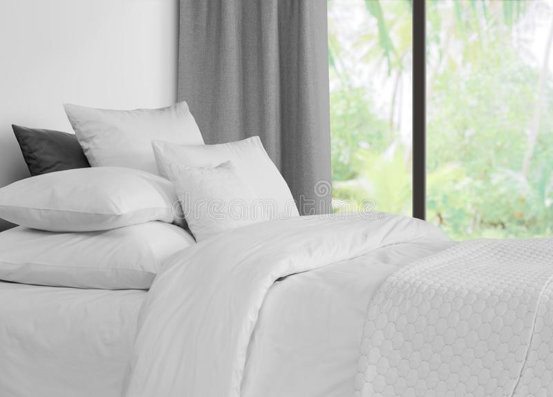 Bed with linen against a window with grey curtains royalty free stock photography