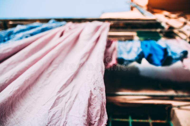 Bed Linen Sheets pink and blue. Hanging drying outside on the house street in Italy Italian tradition habit stock photo