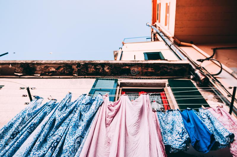 Bed Linen Sheets pink and blue. Hanging drying outside on the house street in Italy Italian tradition habit royalty free stock image