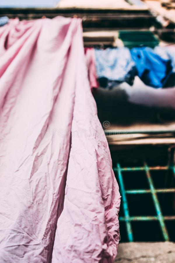 Bed Linen Sheets pink and blue. Hanging drying outside on the house street in Italy Italian tradition habit royalty free stock photography