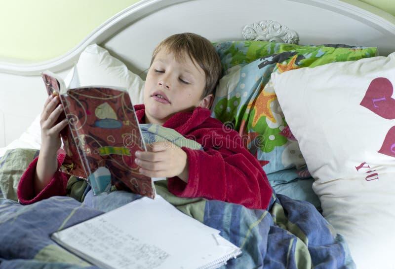 In bed met de griep die schoolwork doet royalty-vrije stock afbeelding