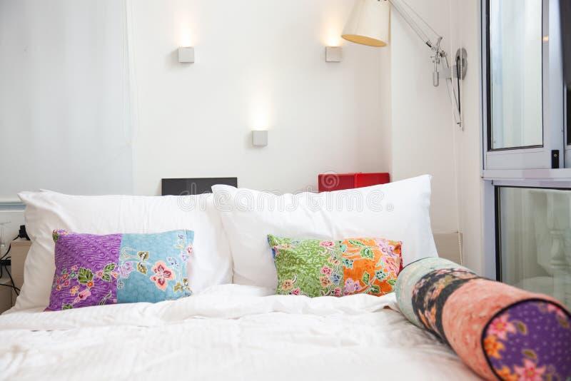 bed met kleurrijke hoofdkussens - comfortabele slaapkamer royalty-vrije stock afbeelding