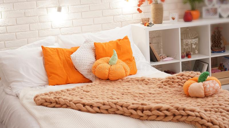 Bed met licht die bedlinnen met een gebreide deken van ruw garen wordt behandeld in de slaapkamer op het bed zijn pompoentextiel royalty-vrije stock afbeelding