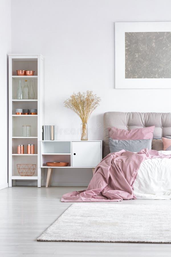 Bed met pastelkleur roze dekbed royalty-vrije stock afbeelding