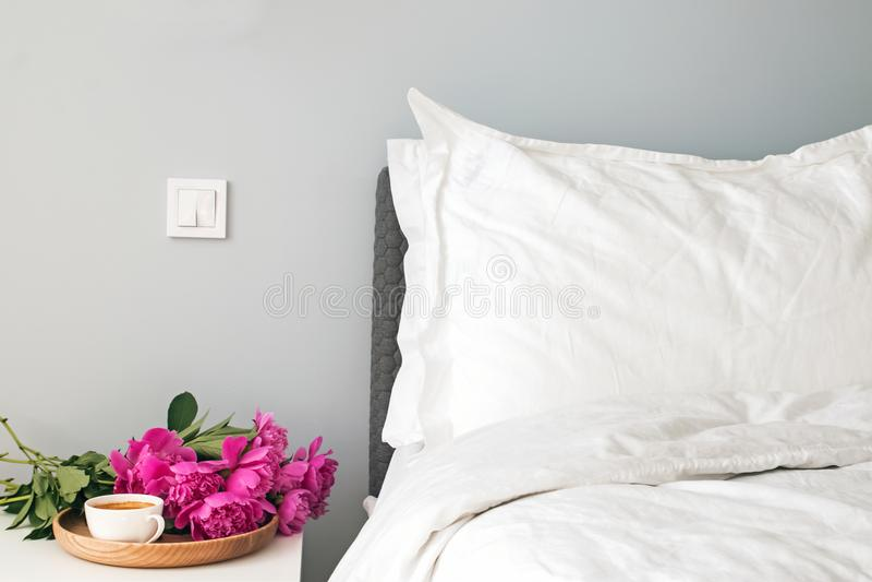 Bed met witte bedbladen en roze pioenen en koffie op nightstand royalty-vrije stock afbeelding