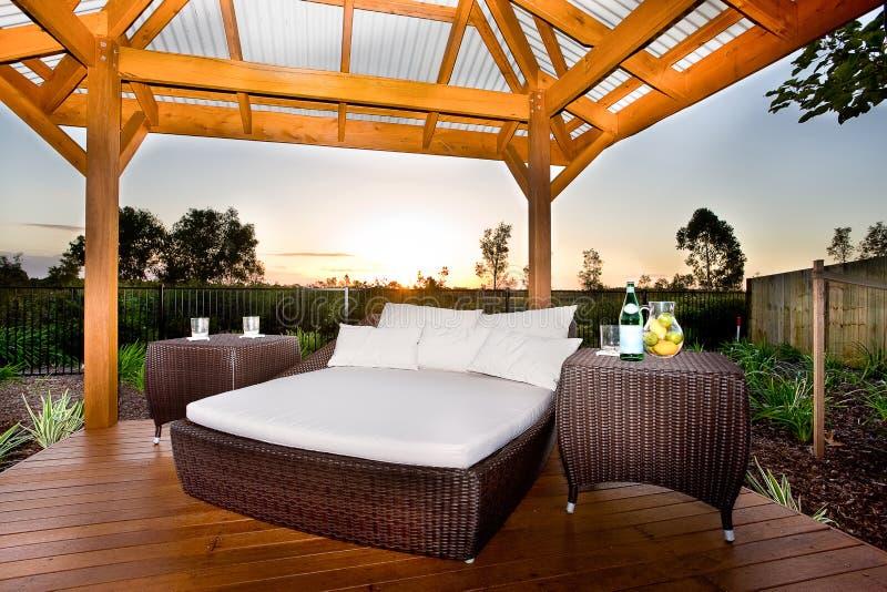 Bed op buitengebied zoals een terras of een ontspannende plaats van een modern huis of een hotel bij zonsondergang royalty-vrije stock fotografie