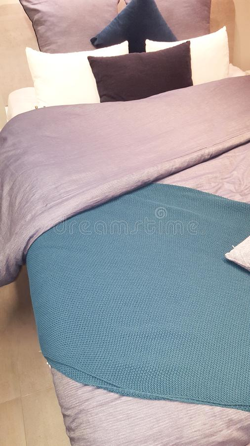 Bed with pink and blue grey bedding in modern bedroom stock photography