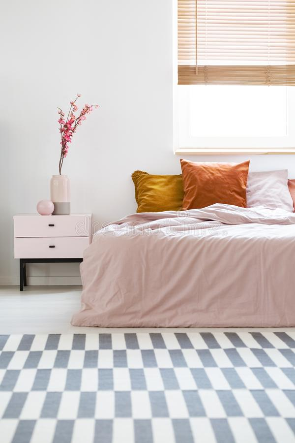 Bed with pink sheets and orange cushions standing in white bedroom interior with carpet, window with wooden blinds and bedside ta royalty free stock images