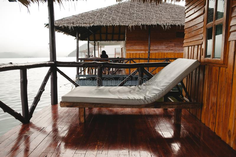 Bed placed on waterfront wooden balcony have other wooden house royalty free stock photo