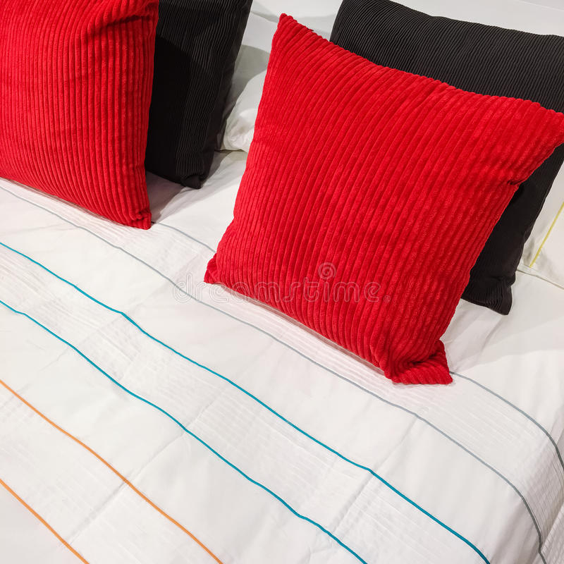 Bed with red and black velveteen cushions. Red and black velveteen cushions on a bed with striped bed linen stock photos