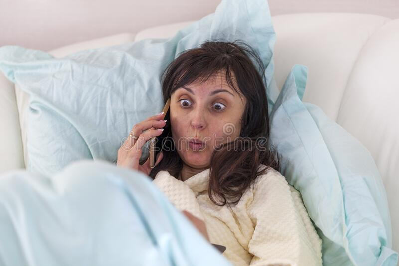 Bed rest at home. Girl brunette in bed speaks on a mobile phone. Surprised facial expression, dilated eyes stock photo