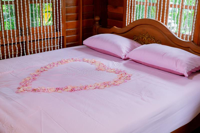Bed room in luxury honeymoon sweet suits. Honey moon bed.Honeymoon, Wedding bed topped with rose and marigold petals. Image for background,,objects, interior stock photo