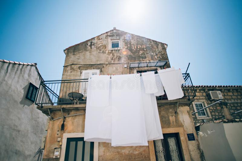White clean laundry hangs on building stock photo