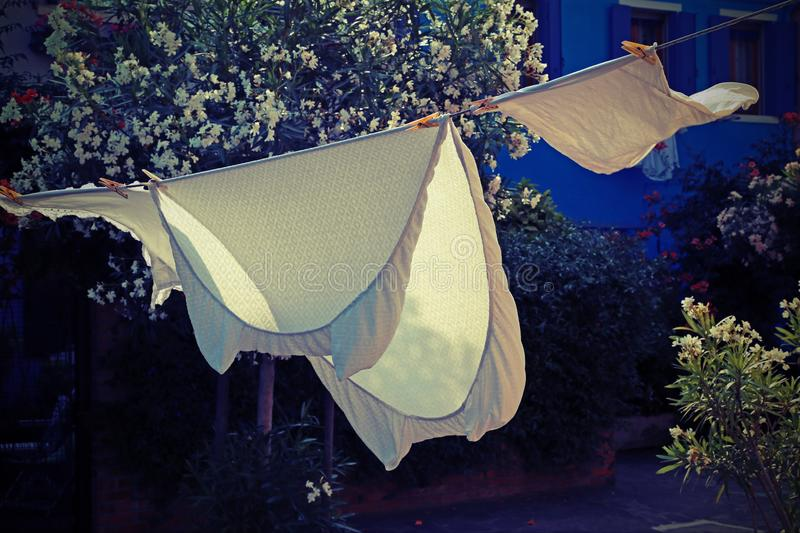White bed sheets spread to dry in the sun royalty free stock photography